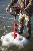 foto of camo  - A man in his camo clothes using a machine to cut through the ice - JPG