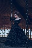 image of fancy-dress  - Mysterious woman dressed in gothic dress posing in ruined building - JPG