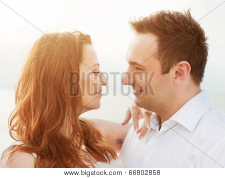 Young happy couple in love in a romantic moment of touching and looking in the eyes on the beach in summer sunshine.