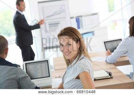 Portrait of smiling woman attending business presentation