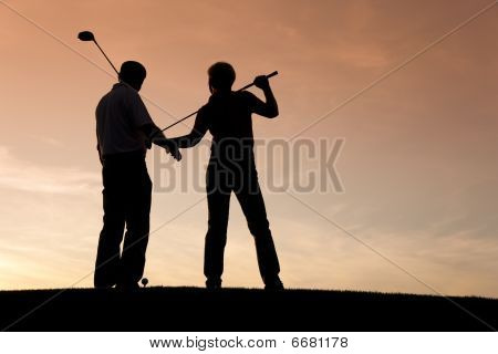 Mature couple playing Golf at sunset