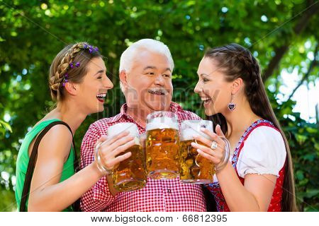 In Beer garden - friends in Tracht, Dirndl and Lederhosen drinking a fresh beer in Bavaria, Germany