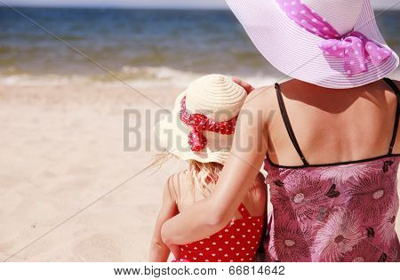 Little Girl Sitting With Her Mother On The Shore Of The Sea