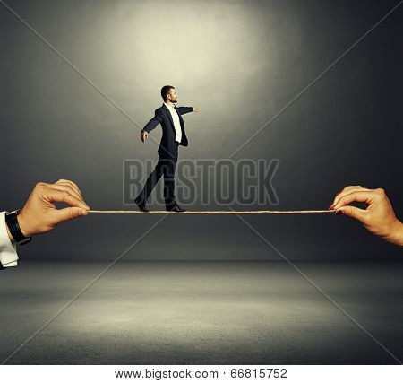 assured businessman walking on the rope over dark background