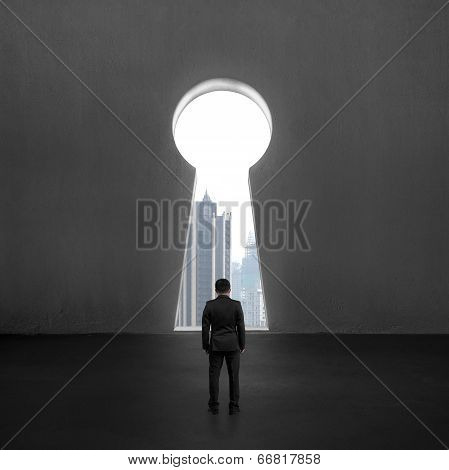 Standing In Front Of Key Shape Hole With City View