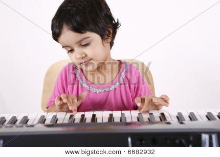 toddler playing a keyboard