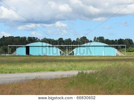 Airplane Hangar Isolated At Airfield With Clouds