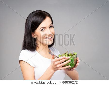 Young, beautiful and healthy teenage girl with a bowl of green salad. Healthy eating concept.