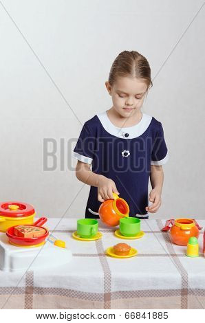 Girl Pouring Milk Into A Cup Of Children's Kitchen