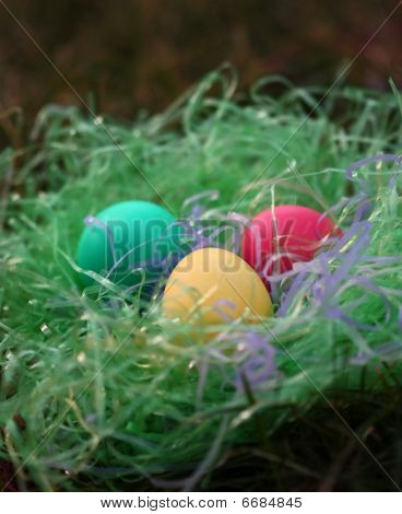 Three Easter eggs in green grass nest