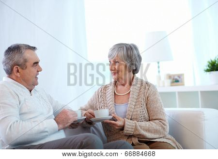 Image of couple of pensioners drinking tea and talking at home