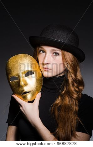 Redhead woman in hat with mask in hypocrisy concept against dark  grey background