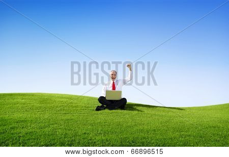 Business Man Outdoors with Computer Arms Raised