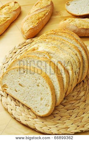 some slices of pan de payes, a round bread typical of Catalonia, Spain, and some demi baguettes on a wooden table