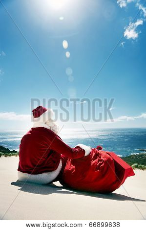 Man in Santa costume sitting on a beach looking at view