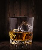 stock photo of whiskey  - Glasses of whiskey with ice cubes on wood background - JPG