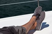 image of hairy  - A pair of hairy man legs in pants and topsiders on white yacht deck - JPG