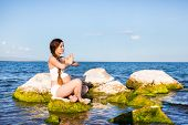 pic of pregnancy exercises  - Pregnant woman in sports bra doing exercise in relaxation on yoga pose on sea - JPG