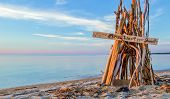 stock photo of teepee  - Wooden teepee on the beach with a handwritten sign - JPG