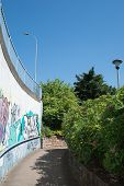 image of underpass  - A curved path follows a curving wall out of a pedestrian underpass - JPG