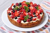 foto of tarts  - berry tart with fresh strawberries raspberries currants mint and cream close up on the table