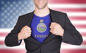 image of kansas  - Businessman opening suit to reveal shirt with state flag  - JPG
