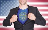 stock photo of nebraska  - Businessman opening suit to reveal shirt with state flag  - JPG