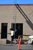 foto of osha  - A roofing company worker climbs a high ladder to the top of a building holding a heavy roll of tarpaper - JPG