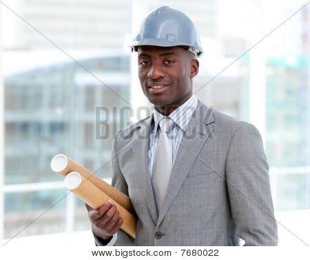 Portrait Of A Charismatic Male Architect Holding Blueprints