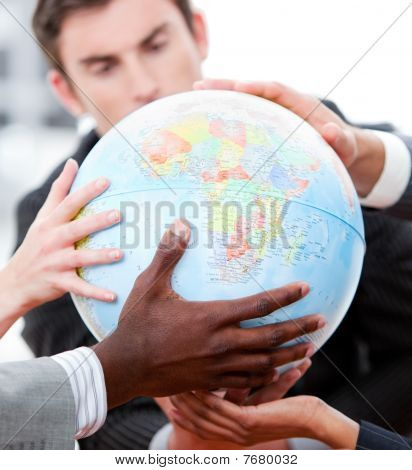 Close-up Of A Business Team Holding A Terrestrial Globe