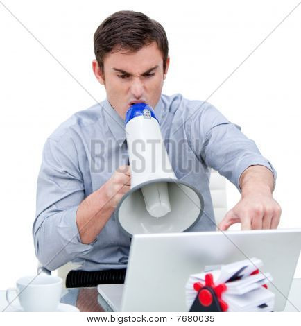 Furious Businessman Yelling Through A Megaphone Sitting At His Desk