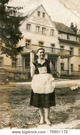 POLANICA ZDROJ, POLAND, CIRCA 1930: Vintage photo of chambermaid in front of a guesthouse
