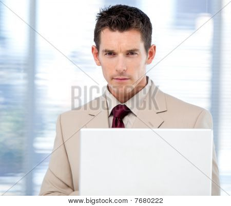 Self-assured Businessman Using A Laptop Standing