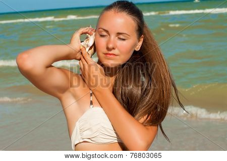 Young girl with long hair in a bikini on a beach with shell