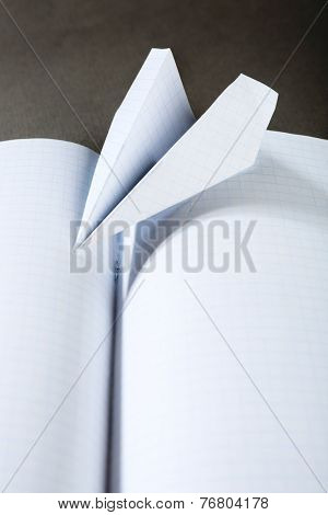 Origami airplane on notebook, close up