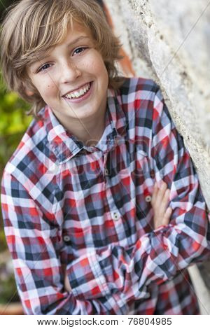 Young happy smiling boy outside wearing a checked plaid shirt