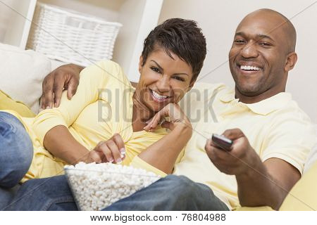 A happy African American man and woman couple in their thirties sitting at home using a remote control, eating popcorn and watching a movie or television