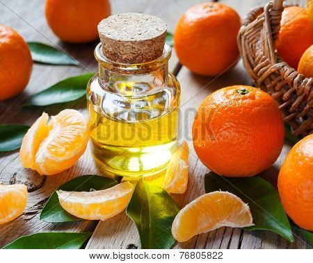Bottle Of Essential Citrus Oil And Ripe Tangerines With Leaves On A Wooden Kitchen Table.