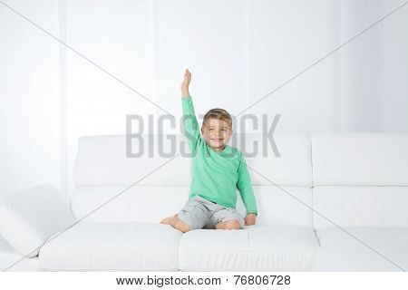 Isolated Young Kid On White Sofa