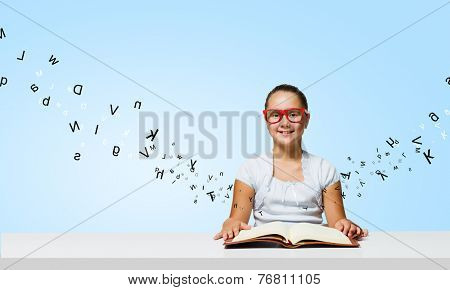 Cute girl of school age in glasses reading book