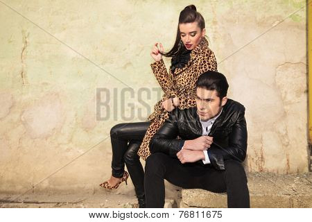 Handsome young fashion man sitting and looking away while his girlfriend is playing with her hair, looking down.