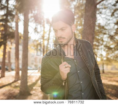 Outdoor picture of a young fashion man looking down while pulling his jacket.