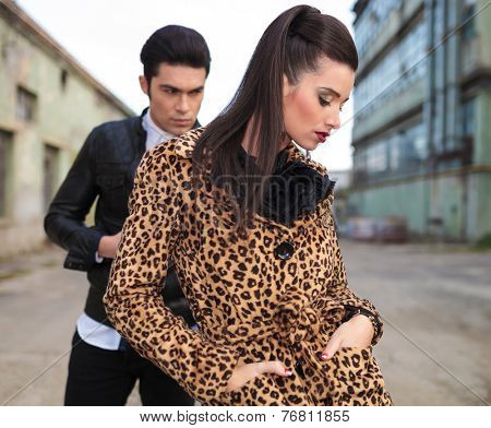Close up picture of a young fashion woman looking down with her hands in pocket while her lover is behind her looking away.