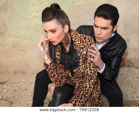 Young fashion man sitting and looking over his girlfriend shoulder, both looking away from the camera.