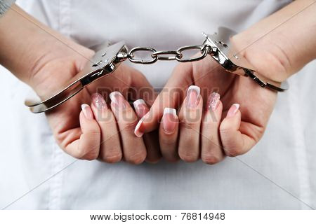 Female hands are handcuffed at  wrist, close-up