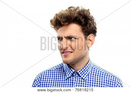 Portrait of a young disgusted man over white background