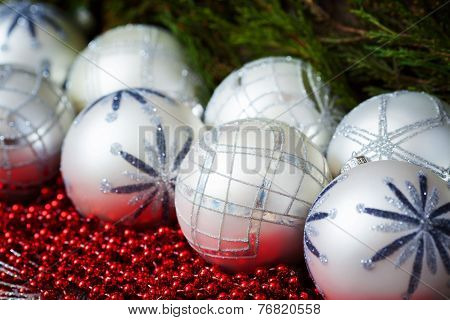 White christmas balls  and red beads with wooden background