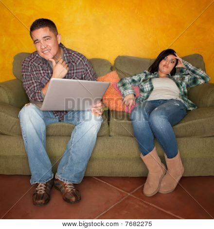 Bored Hispanic Woman Reacting To Man With Computer