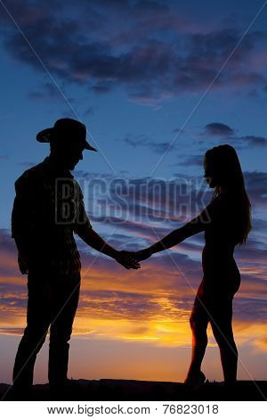 Silhouette Of Cowboy And Woman Touching Hands
