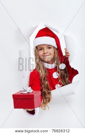 Opening the holidays season - little girl in santa costume offering you a present